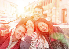 Best friends having fun. Happy cheerful multinational multiracial students in fashionable autumn/winter clothing laughing and joking - happy girls with boys Stock Photo