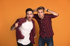 Two handsome men having fun at studio. Best friends having fun at studio. Two men making funny face, posing on orange studio background stock image