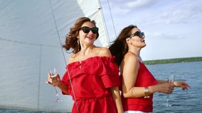 Best friends having party with alcohol on sailboat. Best friends in red clothes and sun glasses having party with wine at sailboat in summer. Two beautiful girls stock video footage