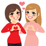 Best Friends Heart. Two best friends girls smiling showing heart gesture with hands Stock Photo