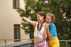 Best friends hugging in park. Phone selfie. Stock Photos