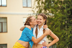 Best friends kiss on the cheek in park. Stock Image