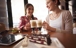 Best friends ladies in cafe. Toned image of best friend having round or chers while drinking delicious coffee in cafe or restaurant. Closeup picture of chocolate Royalty Free Stock Photography