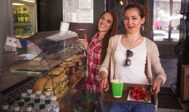 Best friends ladies in cafe. Toned image of happy ladies choosing dishes for eating. Cheerful women having break in cafe or restaurant. Sandwiches and snacks Royalty Free Stock Image