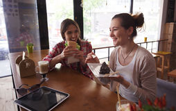 Best friends ladies in cafe. Toned image of happy ladies spending their free time in cafe or restaurant. Pretty women eating sandwich and cafe, drinking coffee Stock Photography