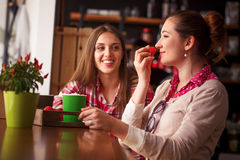 Best friends ladies in cafe. Toned image of pretty females eating fresh strawberries, drinking cups of coffee and communicating in cafe or restaurant Royalty Free Stock Image