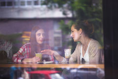 Best friends ladies in cafe. Toned image of pretty girls communicating and talking while eating hamburgers or sandwiches, drinking coffees in cafe or restaurant Stock Photography