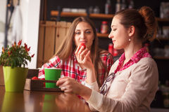 Best friends ladies in cafe. Toned picture of beautiful ladies eating fresh strawberries, drinking cups of coffee and communicating in cafe or restaurant Royalty Free Stock Image