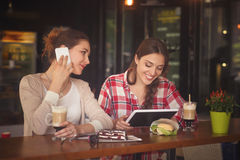 Best friends ladies in cafe. Toned picture of beautiful lady in love communicating over mobile or smart phone while her best friend girl using table PC in cafe Royalty Free Stock Photography