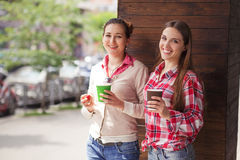 Best friends ladies in cafe. Toned picture of beautiful women posing with cups of coffee outdoors. Happy ladies smiling for camera near cafe or restaurant Royalty Free Stock Image