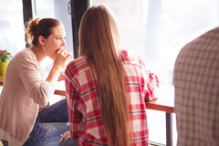 Best friends ladies in cafe. Toned picture of ladies eating delicous sandwiches or snacks while sitting in cafe or restaurant. Pretty girls talking or Royalty Free Stock Image
