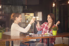 Best friends ladies in cafe. Toned picture of best friends girls having round or cheers while sitting in cafe or restaurant. Women drinking delicious coffe Royalty Free Stock Images