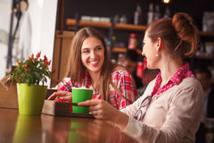 Best friends ladies in cafe. Toned picture of happy smiling best friends drinking cups of coffee and talking or communicating in cafe or restanurant all together Stock Photo