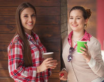 Best friends ladies in cafe. Toned picture of happy smiling girls communicating or talking near restaurant or cafe. Beautiful ladies drinking cups of coffee Stock Photos