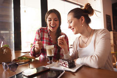Best friends ladies in cafe. Toned picture of ladies looking at cup of latte, smiling and spending their weekends in cafe or restaurant. Pretty girls eating cake Stock Photo