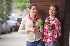Best friends ladies in cafe. Toned picture of pretty ladies drinking cups of coffee outdoors. Happy smiling girls communicating or talking near restaurant or Stock Images
