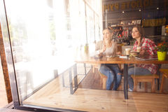 Best friends ladies in cafe. Toned picture of pretty ladies sitting in cafe and looking at window. Beautiful women drinking coffe, eating sandwich or cake Royalty Free Stock Image