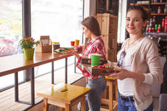 Best friends ladies in cafe. Toned picture of pretty ladies spending free time in cafe or restaurant. Beautiful women gonna drink coffe, eat sandwiches, snacks Stock Photography