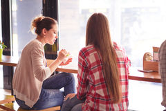 Best friends ladies in cafe. Toned picture of pretty women eating sandwiches and drinking coffee during break. Ladies spending time in cafe or restaurant Stock Photos
