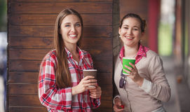 Best friends ladies in cafe. Toned picture of best friends smiling or laughing while holding cups of coffee near cafe or restaurant Royalty Free Stock Photo
