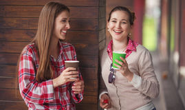 Best friends ladies in cafe. Toned picture of smiling ladies posing with cups of coffee. Happy girls laughing and holding cups of coffee near cafe or restaurant Royalty Free Stock Image