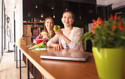Best friends ladies eating in cafe. Toned picture of best friends eating vegetarian sandwiches in cafe or restaurant while looking at camera. Freelance concept Stock Photography