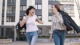 Best friends laugh and fool around while walking down the street. girls enjoy the beautiful weather on the walk. slow. Best friends laugh and fool around while stock video footage