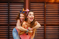 Best friends laughing. Piggyback. Stock Image