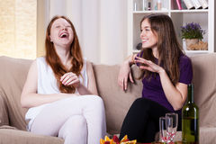 Best friends laughing. Best friends sitting on the sofa talking and laughing Stock Photography