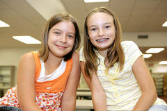 Best Friends in Library. Two cute adolescent girls in the school library stock photo