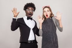 Best friends looking at camera with shocked face and hands up. Studio shot, gray background Stock Photography