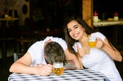 Best friends or lover drink beer in pub. Couple in love on date drinks beer. She knows tricks how to drink and stay. Sober. Man drunk fall asleep on table and stock image