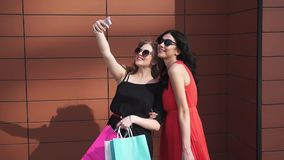 Best friends make selfie after shopping. beautiful girls in sunglasses with shopping bags in hand taking pictures and stock video