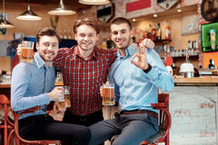 Best friends met in the pub. Meeting with best friends. Cheerful young men in casual wear holding glasses with beer and smiling in the pub Royalty Free Stock Images