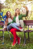 Best friends with one having a broken leg taking a selfie royalty free stock image