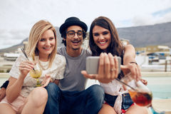 Best friends in party capturing the moment on camera Royalty Free Stock Image