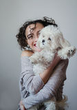 Best friends photo. Photo of two best friends - portrait of the young pretty brunette woman with curly hair and wine lips color holding on her hands puppy white Stock Images