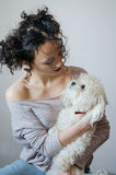 Best friends photo. Photo of two best friends - portrait of the young pretty brunette woman with curly hair and wine lips color holding on her hands puppy white Stock Photo
