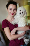 Best friends photo. Photo of two best friends - portrait of the young pretty brunette woman with curly hair and wine lips color holding on her hands puppy white Royalty Free Stock Photos