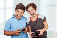 Best friends playing on playstation. At home, crazy emotion of video games, two excited teen boys enjoying competition, laughing and screaming Stock Image