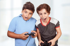 Best friends playing on playstation. At home, crazy emotion of video games, two excited teen boys enjoying competition, winner and loser in the round Stock Photography