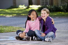 Best friends playing together on driveway Royalty Free Stock Photo