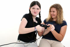 Best Friends Playing Video Games Together. Beautiful tween girls playing video games together. Shot in studio over white Royalty Free Stock Image