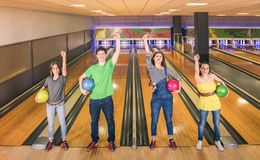 Best friends posing in victory position at bowling track Stock Photos