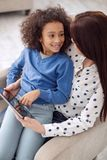 Inspired mother and daughter using a tablet. Best friends. Pretty content curly-haired girl smiling and sitting on her moms lap and her mother holding a tablet Stock Images