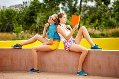 Best friends read diary in park. Royalty Free Stock Images