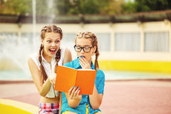 Best friends read diary together in park. Stock Images