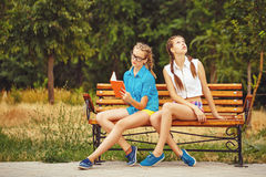 Best friends are reading diary sitting on the bench. Stock Photography