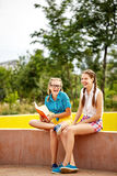 Best friends are reading funny book in park. Stock Photo