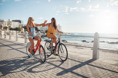 Best friends riding cycles on the seaside promenade Royalty Free Stock Photo